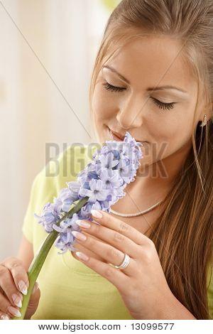 Bela mulher com cheiro de flores com olhos fechados, segurando a flor com as duas mãos.