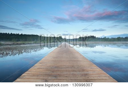 wooden road on water at misty sunrise