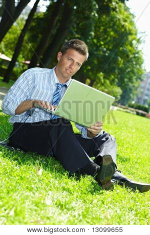 Relaxed businessman sitting in grass beside laptop computer, reading newspaper.