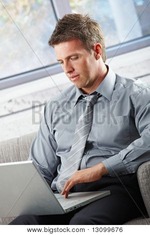 Smart businessman with laptop in lap typing on keyboard concentrating looking at screen.