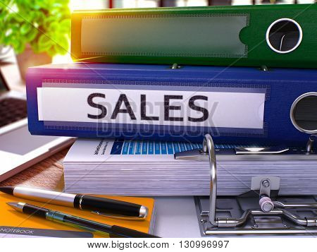 Blue Ring Binder with Inscription Sales on Background of Working Table with Office Supplies and Laptop. Sales - Toned Illustration. Sales Business Concept on Blurred Background. 3D Render.