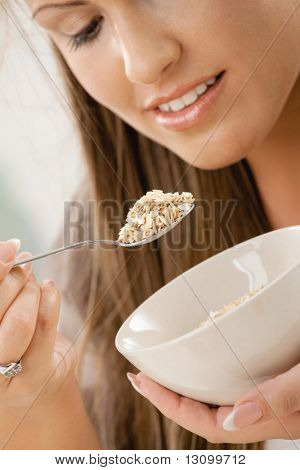 Beautiful young woman eating breakfast cereal. Selective focus on spoon.