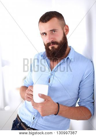 Young man standing near wall and holding cup of coffee