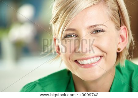 Closeup retrato de mulher jovem feliz, vestindo a camisa verde, sorrindo.