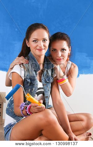 Two Beautiful young woman doing wall painting, sitting