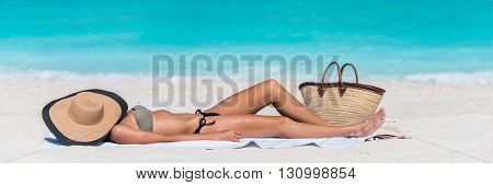 Beach woman sunbathing lying down sleeping on white sand covering her face with straw hat for uv sun rays protection on turquoise ocean background. Vacation girl relaxing tanning on summer travel.