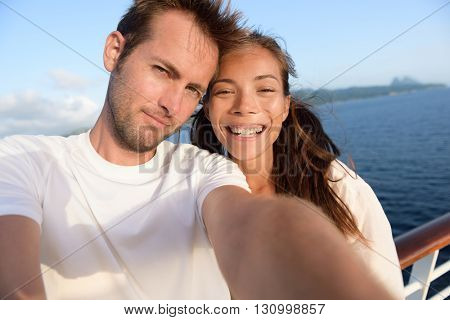 Selfie couple taking holiday self-portrait picture of themselves. Happy multiracial friends having fun together on cruise vacation in Caribbean destination taking smartphone photos as summer memories.