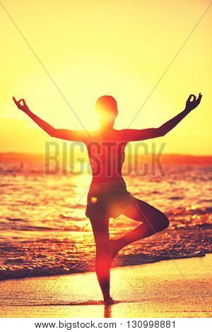 Wellness of mind - Yoga woman standing on one leg doing tree pose with open raised arms in sunset flare doing morning exercise routine on tropical beach. Mindfulness and meditation concept.