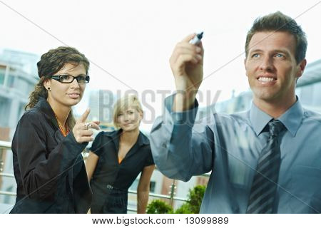 Business team planning, businessman thinking drawing diagram on window. Outdoor of office on terrace. Focus on businesswoman.