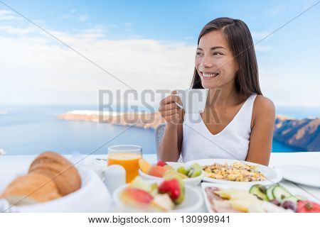 Asian Woman drinking hot drink at morning Breakfast table. Beautiful elegant lady having coffee cup on luxury hotel terrace with sea view at resort restaurant on Oia Santorini island, Greece.