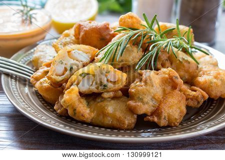 In the foreground shrimps in crispy dough on a plate with rosemary, in the background cutlery, glass of water, lemon, herbs and bowl with the sauce. Shrimps in pastry for lunch. Horizontal. Close-up.