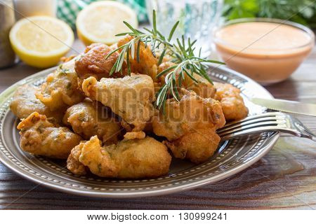 In foreground shrimps in crispy dough on a plate with rosemary, cutlery, in background glass of water, lemon, herbs, salt, pepper, bowl with sauce. Shrimps in pastry for lunch. Horizontal. Close.
