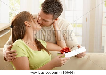 Kissing couple sitting on sofa, man handing present over to woman.