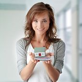 stock photo of house rent  - Beautiful young woman holding euros bills and house model over white  - JPG