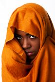 stock photo of nomads  - Beautiful mysterious african nomadic bedouin female face in ocher Earth tone head wrap scarf looking - JPG