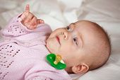 foto of babygro  - 5 months baby girl laying on white sheet - JPG