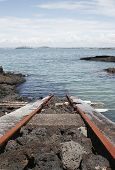 picture of scoria  - a train track runs from a boat shed into the water of the hauraki gulf - JPG