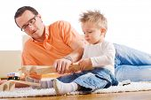 Father and two year old child playing together with wooden toy train. Sitting on floor at home.
