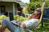 Healthy senior man is his elderly 70s sitting outdoor in garden at home and using laptop computer to