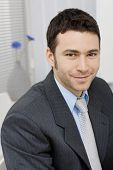 stock photo of young adult  - Portrait of happy young businessman at office - JPG