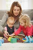 stock photo of nuclear family  - Mum playing on floor with two children at home - JPG