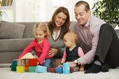 foto of nuclear family  - Happy family of four playing on floor  in living room sitting on floor in front of sofa - JPG