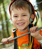 stock photo of little boy  - Portrait of happy little boy having fun in adventure park smiling to camera wearing mountain helmet and safety equipment - JPG