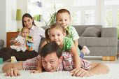 image of nuclear family  - Happy family having fun posing for camera on floor of in living room at home - JPG