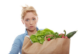 picture of heavy bag  - Young woman holding a grocery bag full of fresh and healthy food isolated on white background - JPG