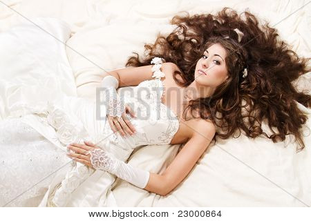 Bride With Curly Long Hair Lying Over White. High Angle View. Fashion Wedding Shoot.