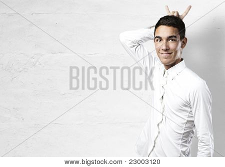 portrait of handsome young man doing horn symbol over white wall