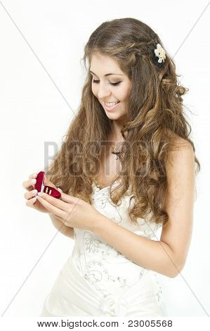 Bride Holding Red Box With Golden Wedding Rings. Smiling And Looking At Rings. Over White