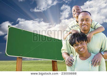 Attraktive afroamerikanische Familie vor leeren Green Road Sign bereit für Ihre Botschaft.
