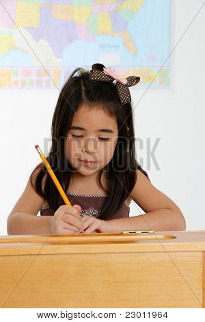 Young Girl Writing at Her Desk in School