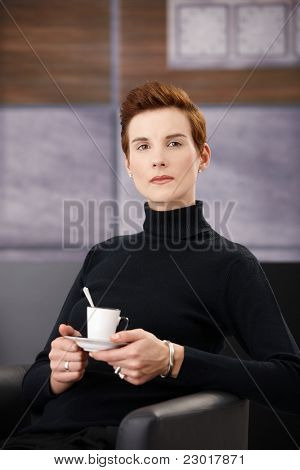 Smart woman wearing polo-neck top having coffee in armchair, holding saucer, looking at camera.?