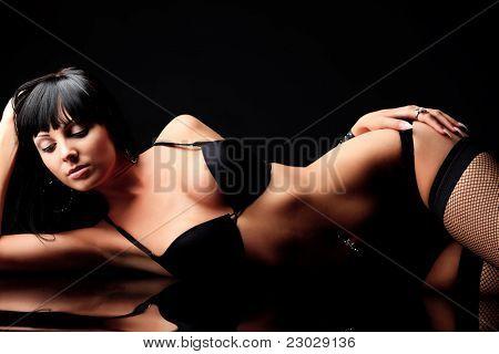 Foto de uma mulher sexy em lingerie preta sobre fundo preto.