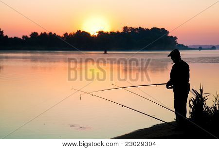 Silhouette of a man fishing in a sunse