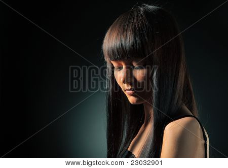 Portrait of beautiful model with long straight hair over dark background.