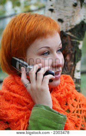 Junge Rothaarige Frau im roten Schal spricht In Mobile-Phone