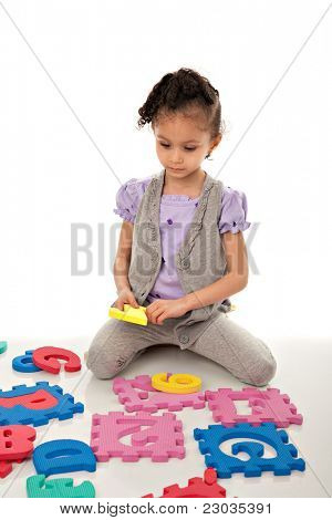 Little Cute Girl Solving Number Alphabet Puzzle