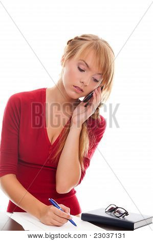 Young Woman Student At Table Writes And Talking In Cell Phone