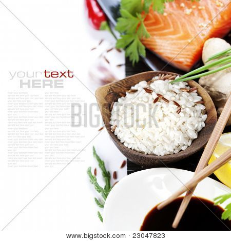 traditional asian ingredients (Fresh salmon steak filet, uncooked rice, ginger, lemon,  soy sause and chopsticks) over white with sample text