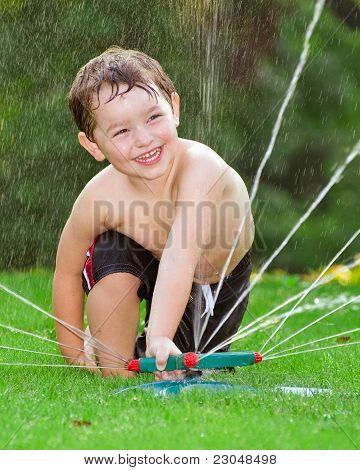 Jovem rapaz ou garoto esfria jogando em aspersão de água em casa no seu quintal, em dia quente de Verão