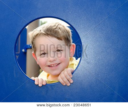 Cute young boy or kid peeks through hole at playground outdoors at park.
