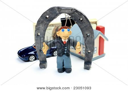 Shot of a plasticine businessman in a suit standing with a horseshoe, car, house and money. Isolated over white background.