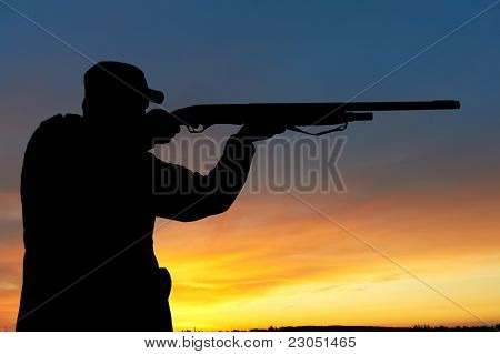 hunter aiming the hunting rifle during a hunt at sunrise
