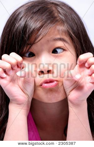 Little Girl Making A Funny Face And Crossing Eyes
