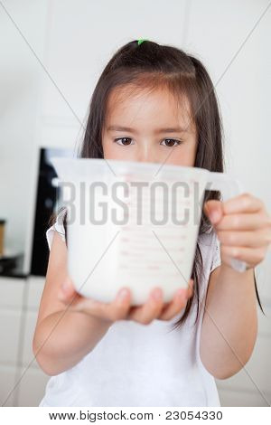Little cute girl holding milk in a measuring mug