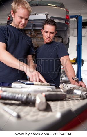 Two mechanics looking at work order and discussing repairs