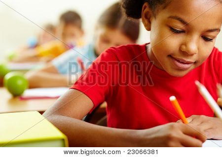 Portrait of lovely girl drawing with crayons at lesson